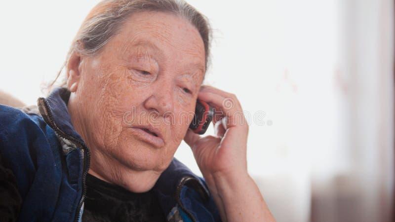 Старшая дама - старуха говорит телефон клетки, портрет стоковые изображения