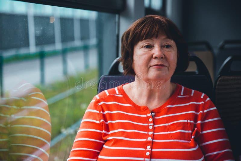 Старшая бабушка коммутируя трамваем стоковая фотография