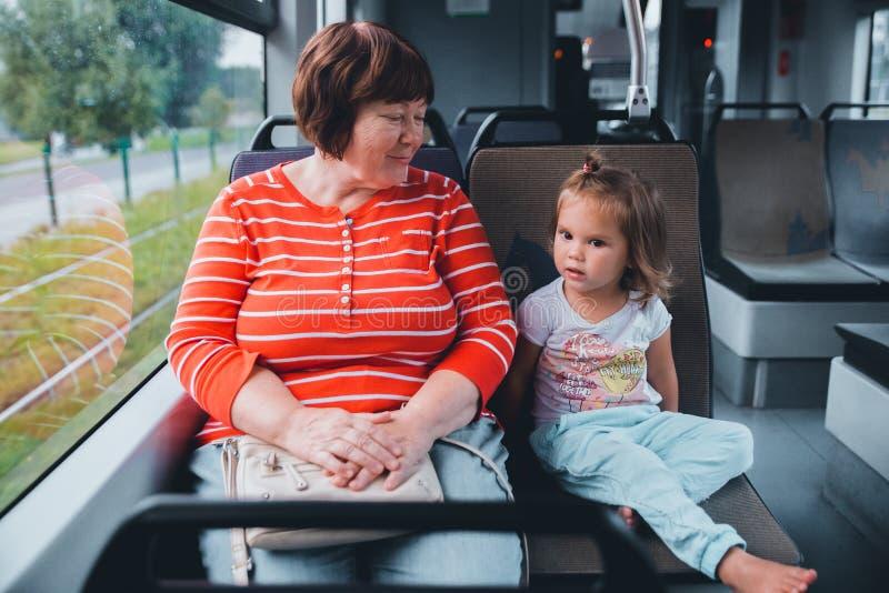 Старшая бабушка с младенцем коммутируя трамваем стоковое фото rf