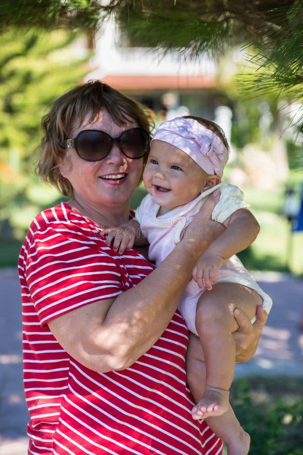 Старшая бабушка с младенцем на открытом воздухе в саде стоковая фотография