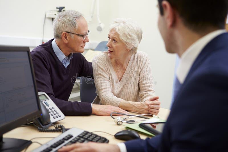Старшая встреча пар с консультантом в больнице стоковое изображение rf
