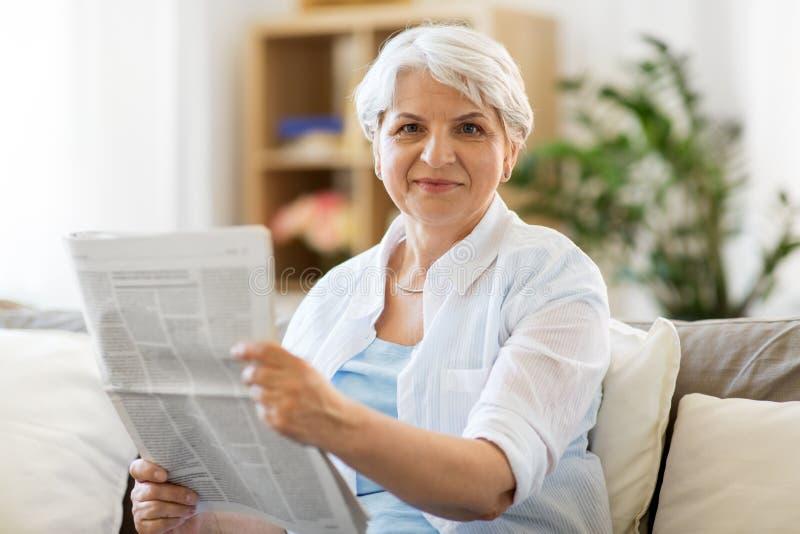 Старшая газета чтения женщины дома стоковое фото rf