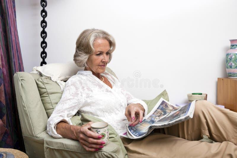 Старшая газета чтения женщины пока ослабляющ дома стоковые изображения rf