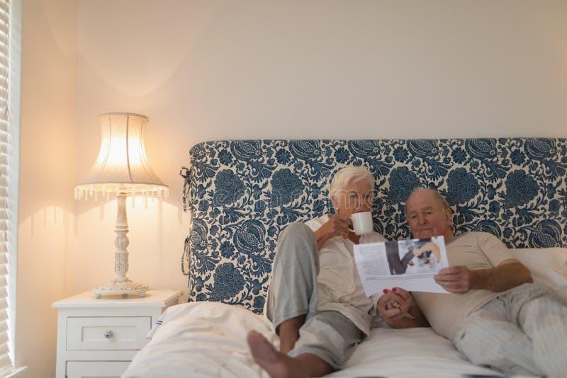 Старшая газета чтения пар в спальне стоковые изображения
