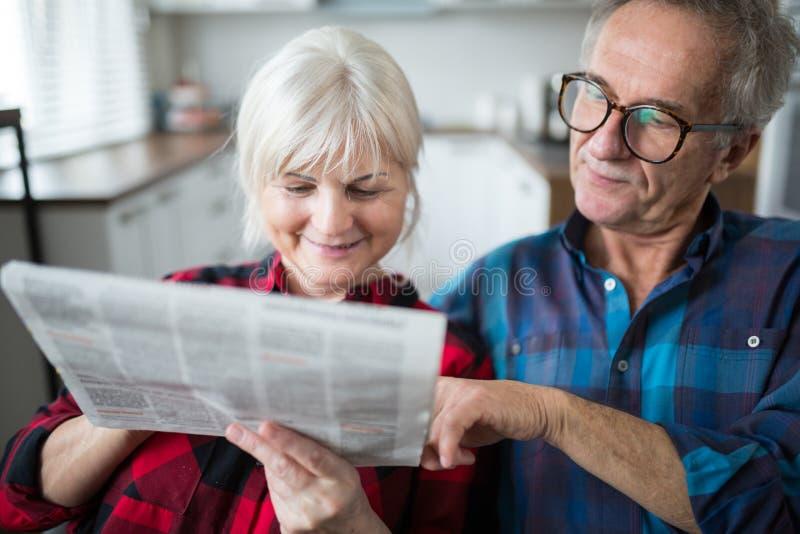 Старшая газета чтения пар совместно стоковое изображение