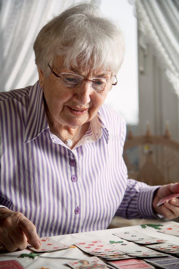 Старшая дама играя карты пасьянса дома стоковые фотографии rf