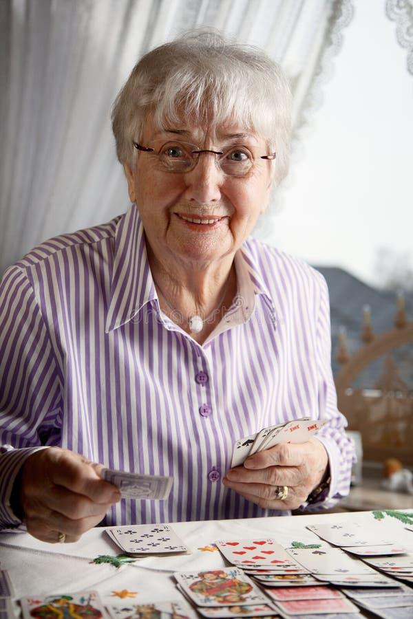 Старшая дама играя карты пасьянса дома стоковое изображение
