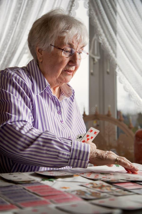 Старшая дама играя карты пасьянса дома стоковые фото