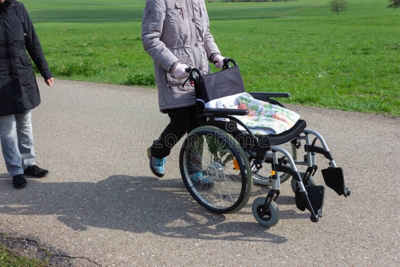 старшая дама нажимая кресло-коляску стоковые фотографии rf
