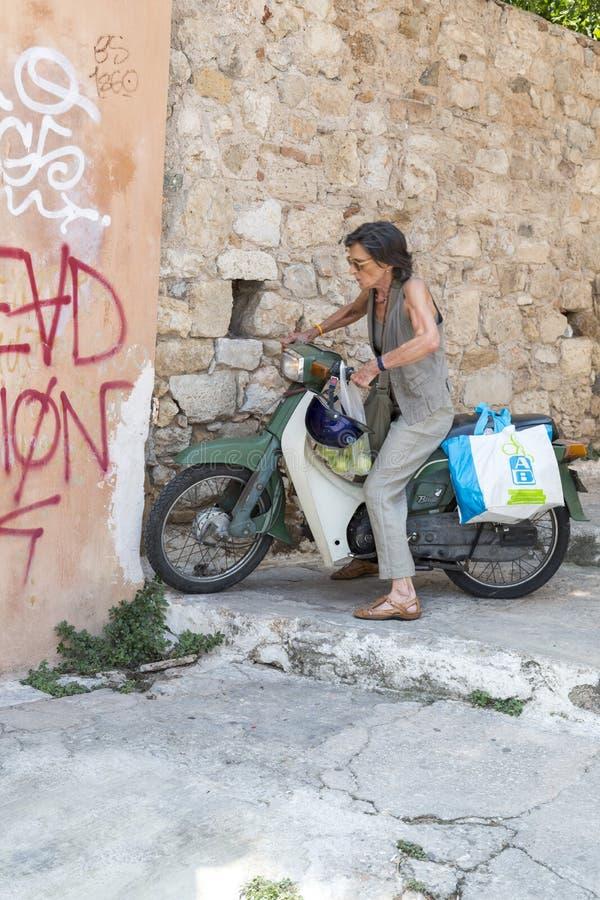 Старшая дама на мотоцилк в Афинах стоковые фото