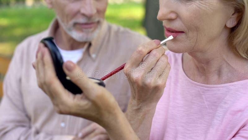 Старшая дама прикладывая губную помаду, концепцию красоты, косметики про-времени, уход за лицом стоковое фото