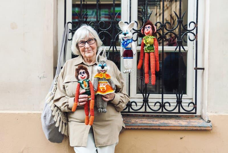 Старшая дама продавая handmade связанные игрушки на улице стоковые изображения