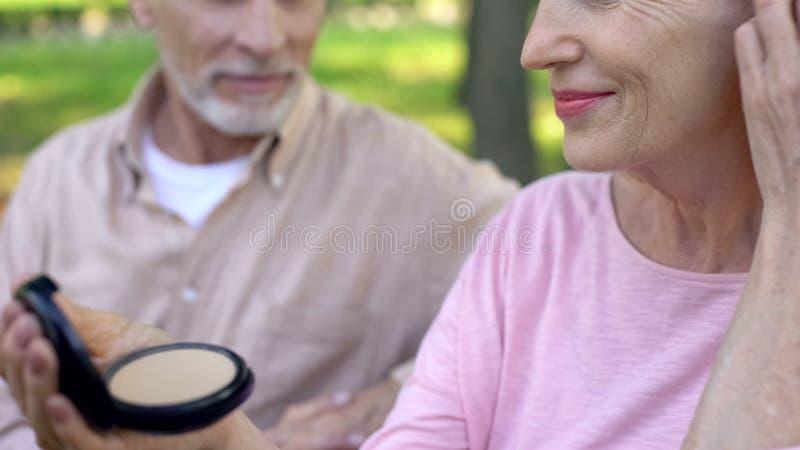 Старшая дама смотря в зеркале кармана, мягкой коже в старости, уходе за лицом, составляет стоковая фотография