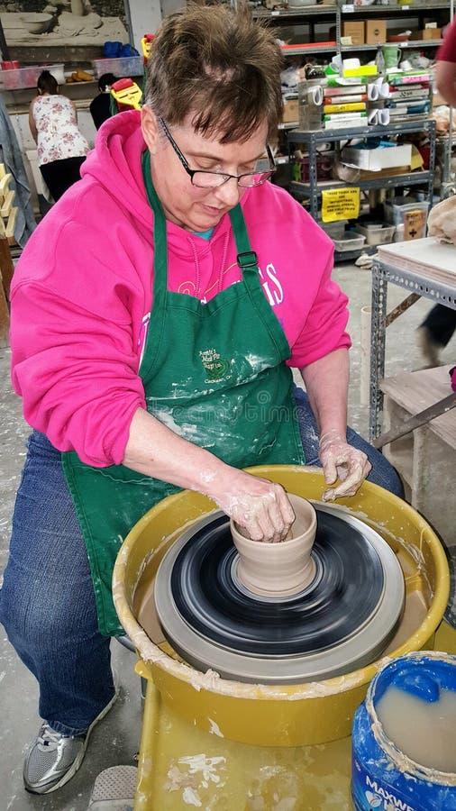 Старшая дама woking с глиной a на колесе гончаров стоковое фото rf