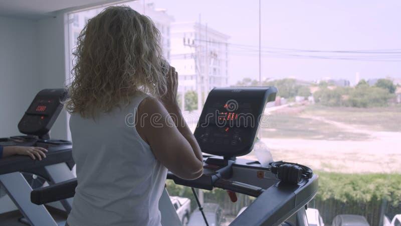 Старшая женщина включена на третбане в спортзале женский говорить по телефону делая третбан стоковые фото
