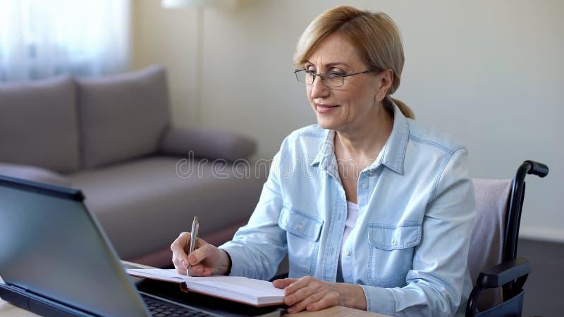Старшая женщина в изучать кресло-коляскы онлайн и делать примечания, видео- уроки стоковые изображения rf