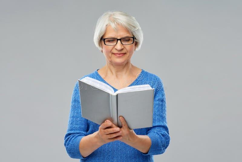 Старшая женщина в книге чтения стекел стоковое фото rf