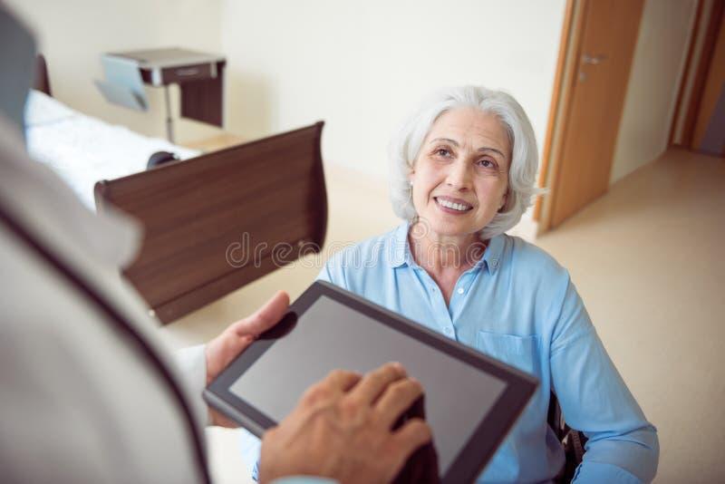 Старшая женщина в кресло-коляске с доктором стоковая фотография rf