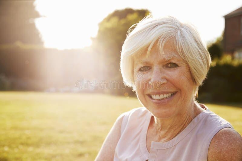 Старшая женщина в саде, усмехаясь к камере, конец вверх стоковые фото