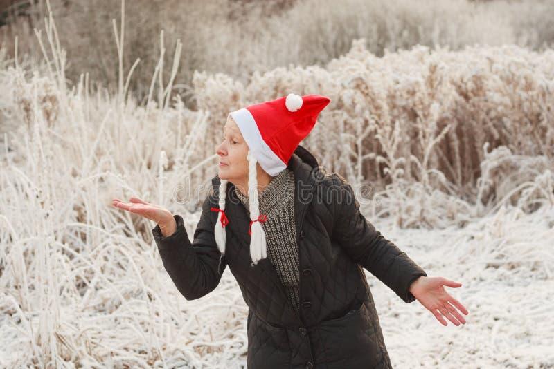 Старшая женщина в смешной шляпе santa при отрезки провода показывая открытую ладонь руки для продукта или текста стоковое фото rf