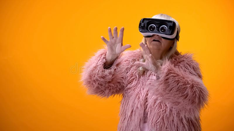 Старшая женщина в смешном пальто и шлемофоне VR играя видеоигру, лидиру стоковое изображение