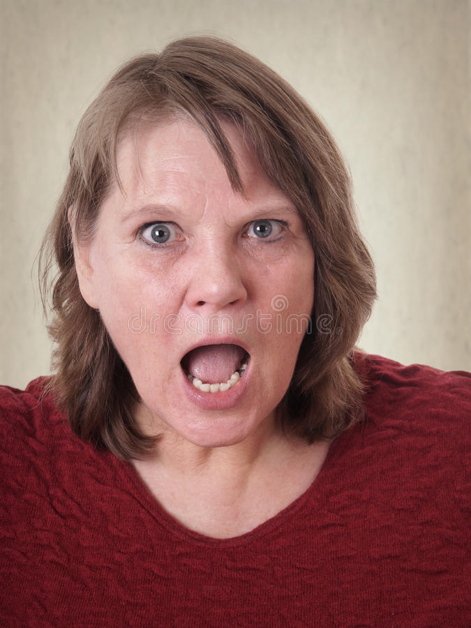 Shocked mature woman with hands on cheeks stock photo