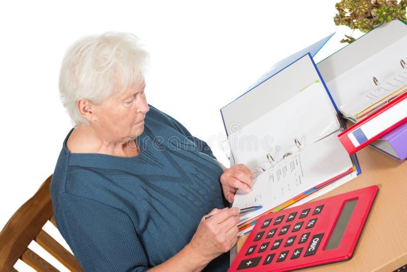 Старшая женщина делая ее учет стоковая фотография rf