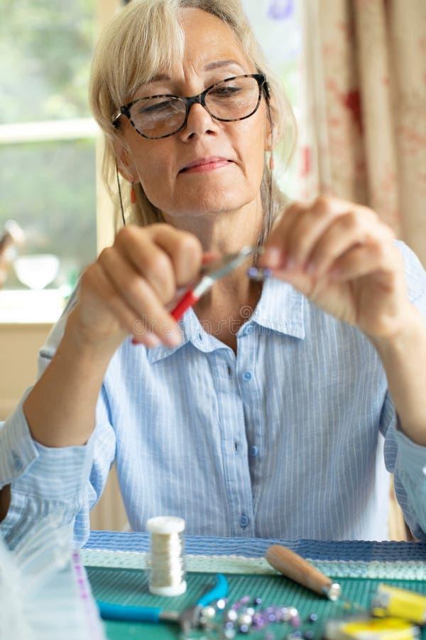 Старшая женщина делая серьги украшений дома стоковая фотография rf