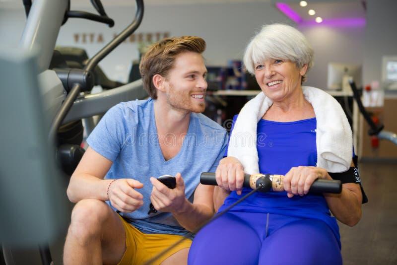 Старшая женщина делая спорт работает с тренером или личным тренером стоковые изображения rf