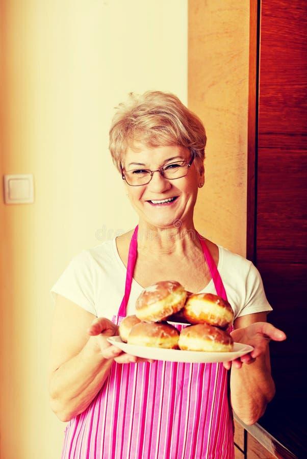 Старшая женщина держа плиту с donuts стоковые фотографии rf