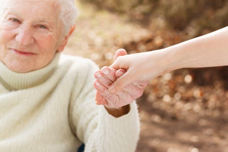 Старшая женщина держа руки с молодой дамой стоковые изображения rf