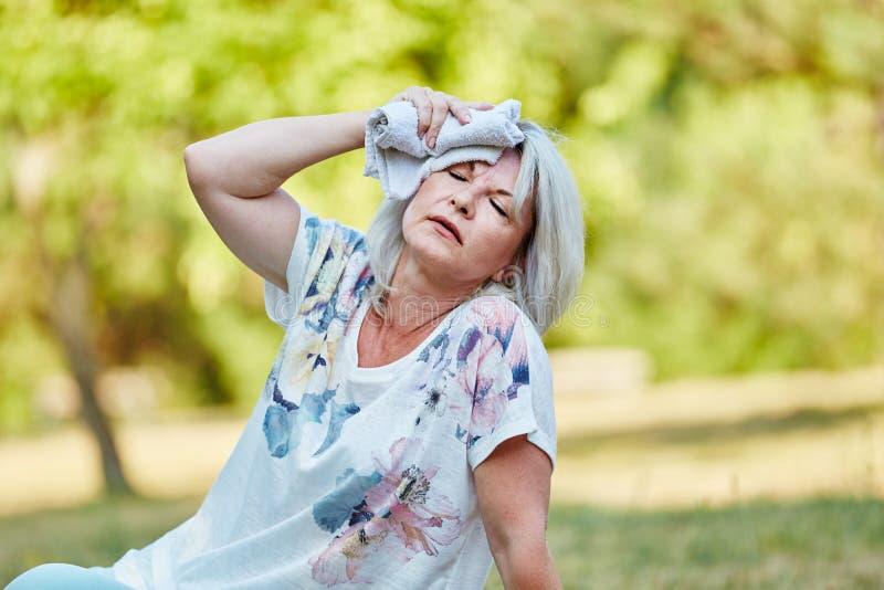 Старшая женщина держит влажную ткань на ее лбе стоковая фотография rf