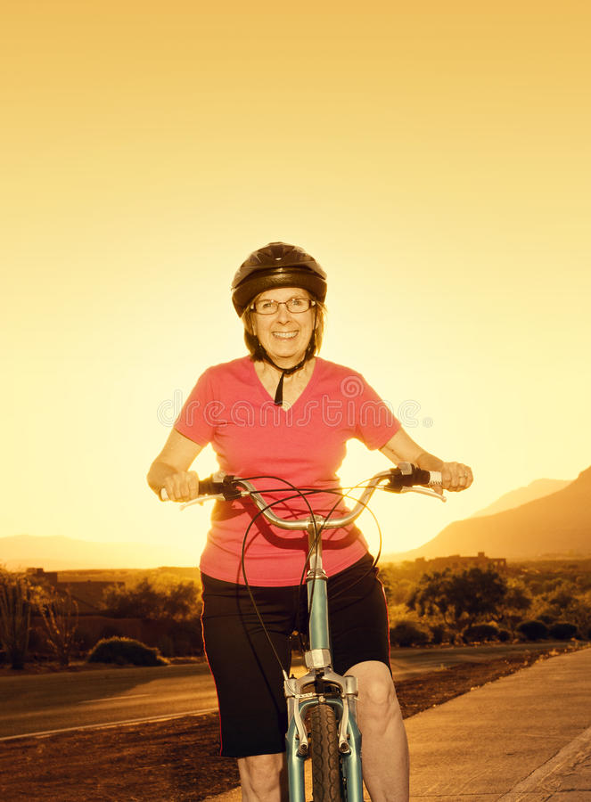 Старшая женщина ехать велосипед на заходе солнца стоковое изображение