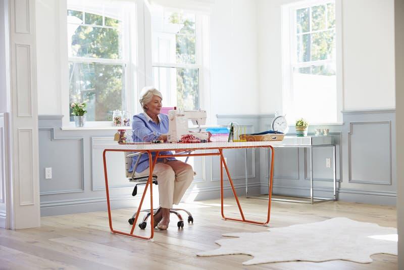 Старшая женщина делая одежды используя швейную машину дома стоковые изображения rf