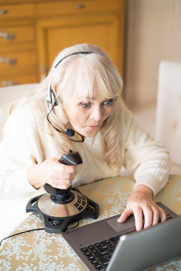 Старшая женщина играет видеоигры с кнюппелем на ноутбуке стоковые фотографии rf