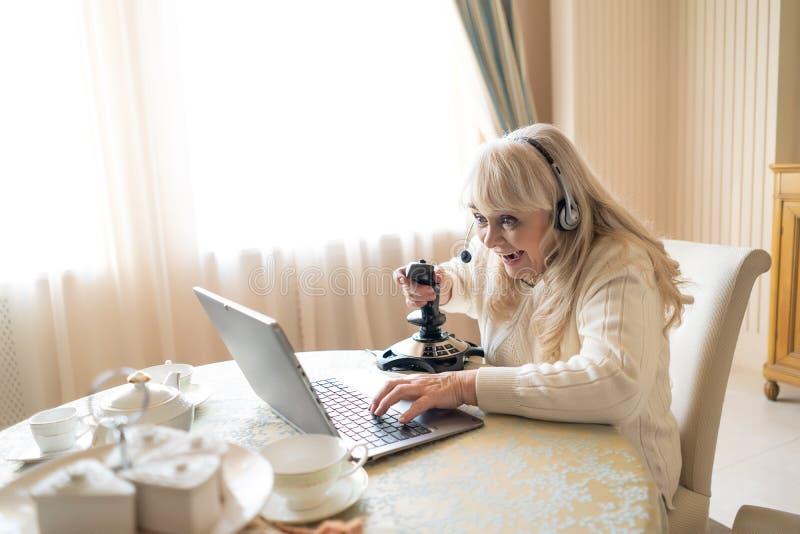 Старшая женщина играет видеоигры с кнюппелем на ноутбуке стоковое фото