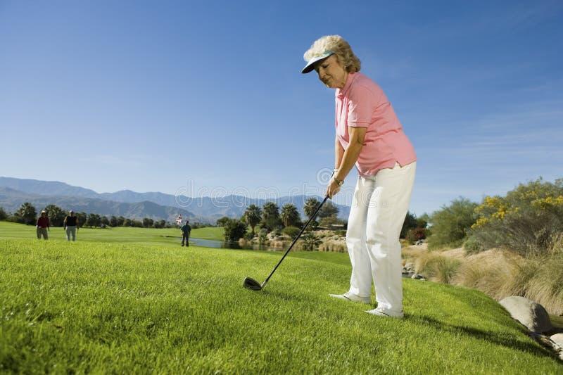Старшая женщина играя гольф стоковые изображения rf