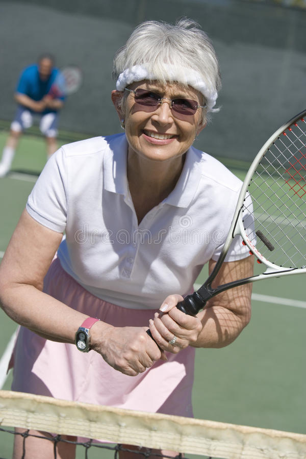 Старшая женщина играя теннис стоковое фото rf