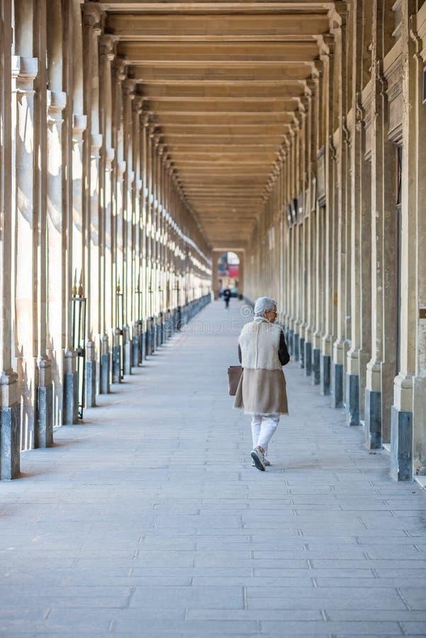 Старшая женщина идя в Palais Royal в Париже, Франции стоковые фото