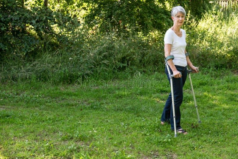 Старшая женщина идя с костылями стоковое фото