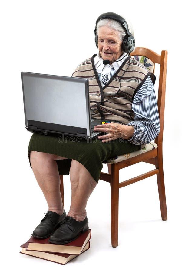 Старшая женщина используя портативный компьютер над белизной стоковая фотография rf