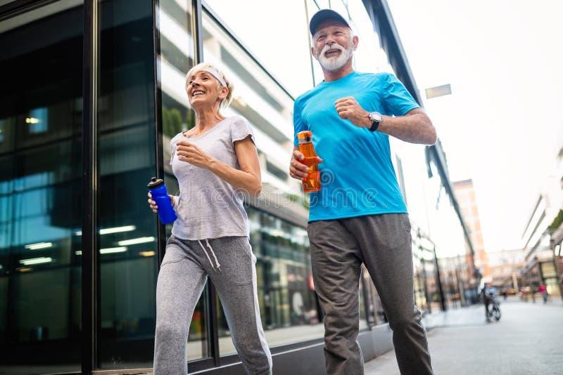 Старшая женщина и человек бежать делающ тренировки фитнеса стоковые фото