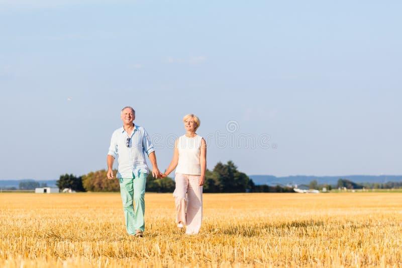 Старшая женщина и человек держа руки имея прогулку стоковое фото