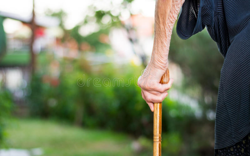 Старшая женщина идя с тросточкой стоковое изображение