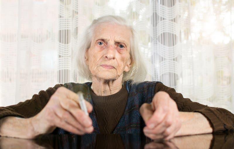 Старшая женщина куря сигарету стоковые фотографии rf