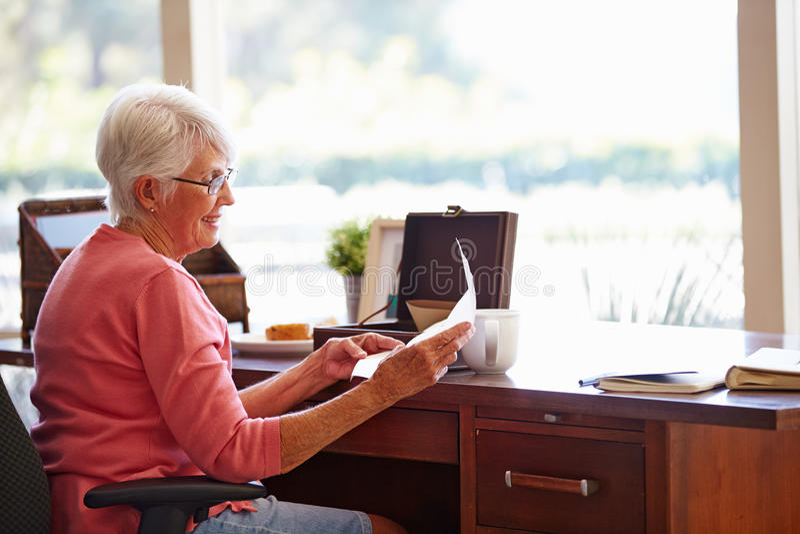 Старшая женщина кладя письмо в коробку Keepsake стоковое фото rf