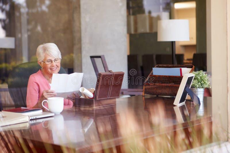 Старшая женщина кладя письмо в коробку Keepsake стоковая фотография rf