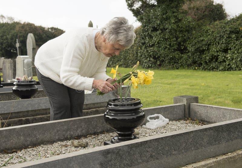 Старшая женщина кладя цветки на могилу стоковая фотография rf