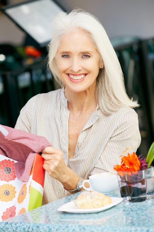 Старшая женщина наслаждаясь заедк на напольном кафе стоковая фотография