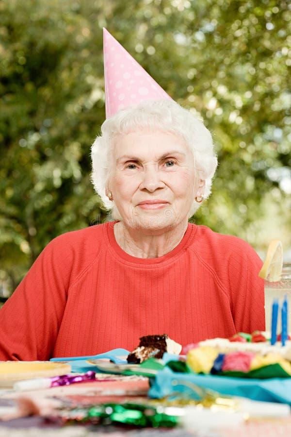Старшая женщина на вечеринке по случаю дня рождения стоковое изображение rf